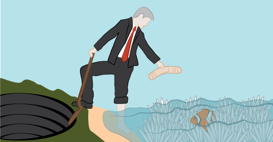 A man wearing a suit is giving a bandaid to a bleached coral reef while digging a coal mine with a shovel.